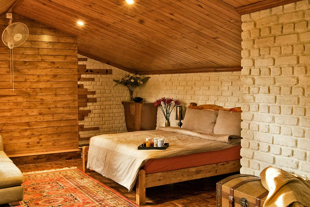 Brick walls, double bed, wooden roof and flooring