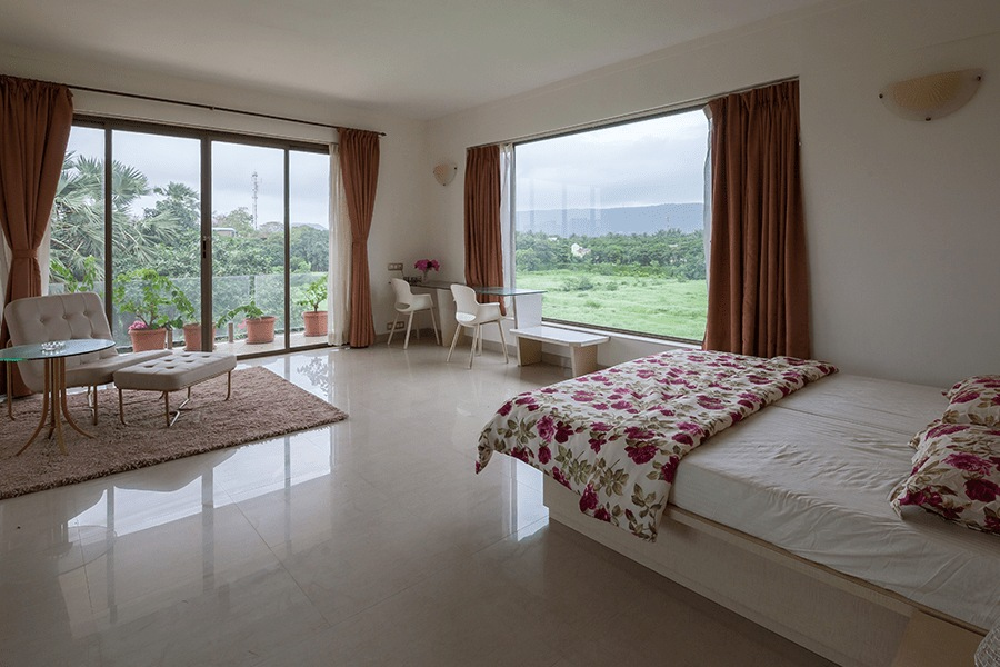 Spacious bedroom with double bed, sitting area, side table and lawn-facing, pet friendly space