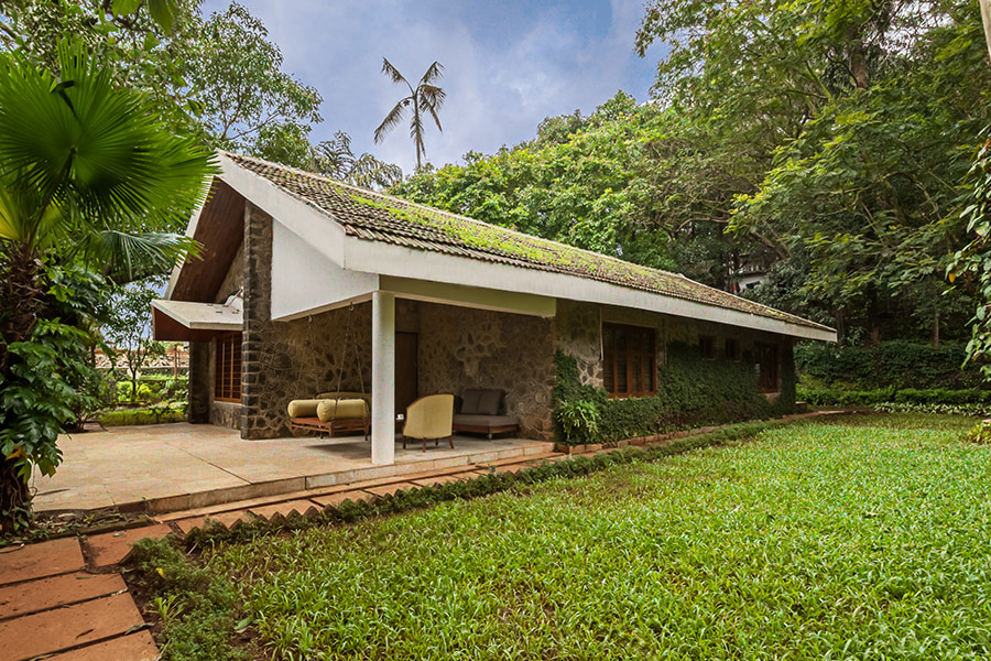 Stone house with roof, swing, front porch and green lawn where pets can play