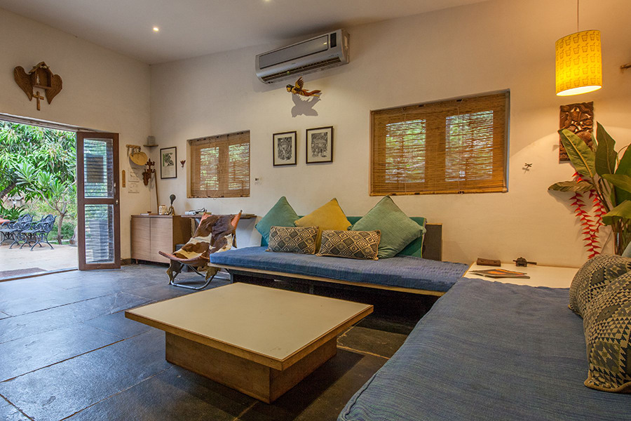 Living room with sofa, cushions, plants, coffee table and facing swimming pool