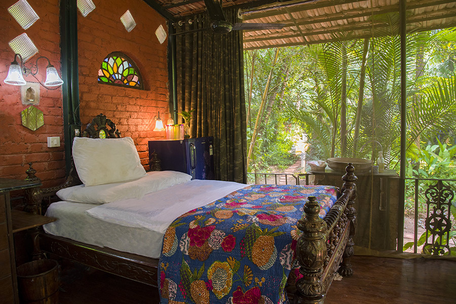 Bedroom with double bed, quirky decor, brick walls and garden-facing