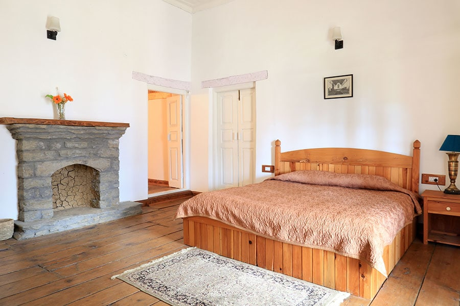 Spacious bedroom in Manali villa, bright interiors and fireplace