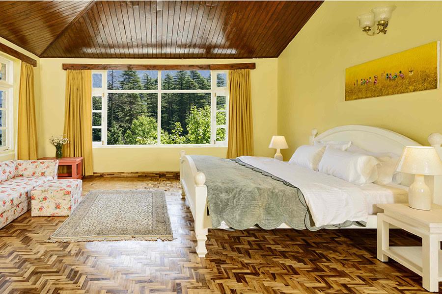 Cozy bedroom in Manali villa, wooden roof and floor, pastel yellow walls