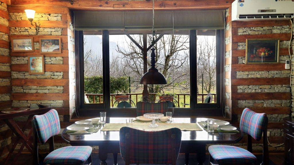 Cozy dining area, wooden and stone interiors, lawn facing