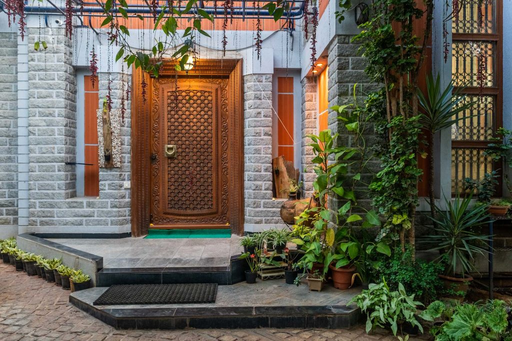 Beautiful entrance to villa in Bangalore, carved wooden front gate, house plants