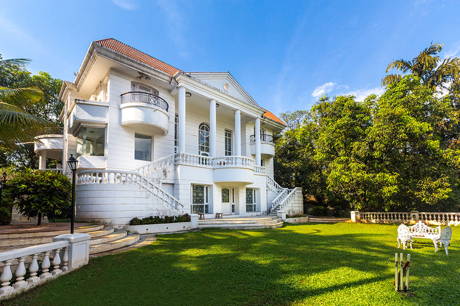 White palace structure with vast lawn in a villa near Mumbai