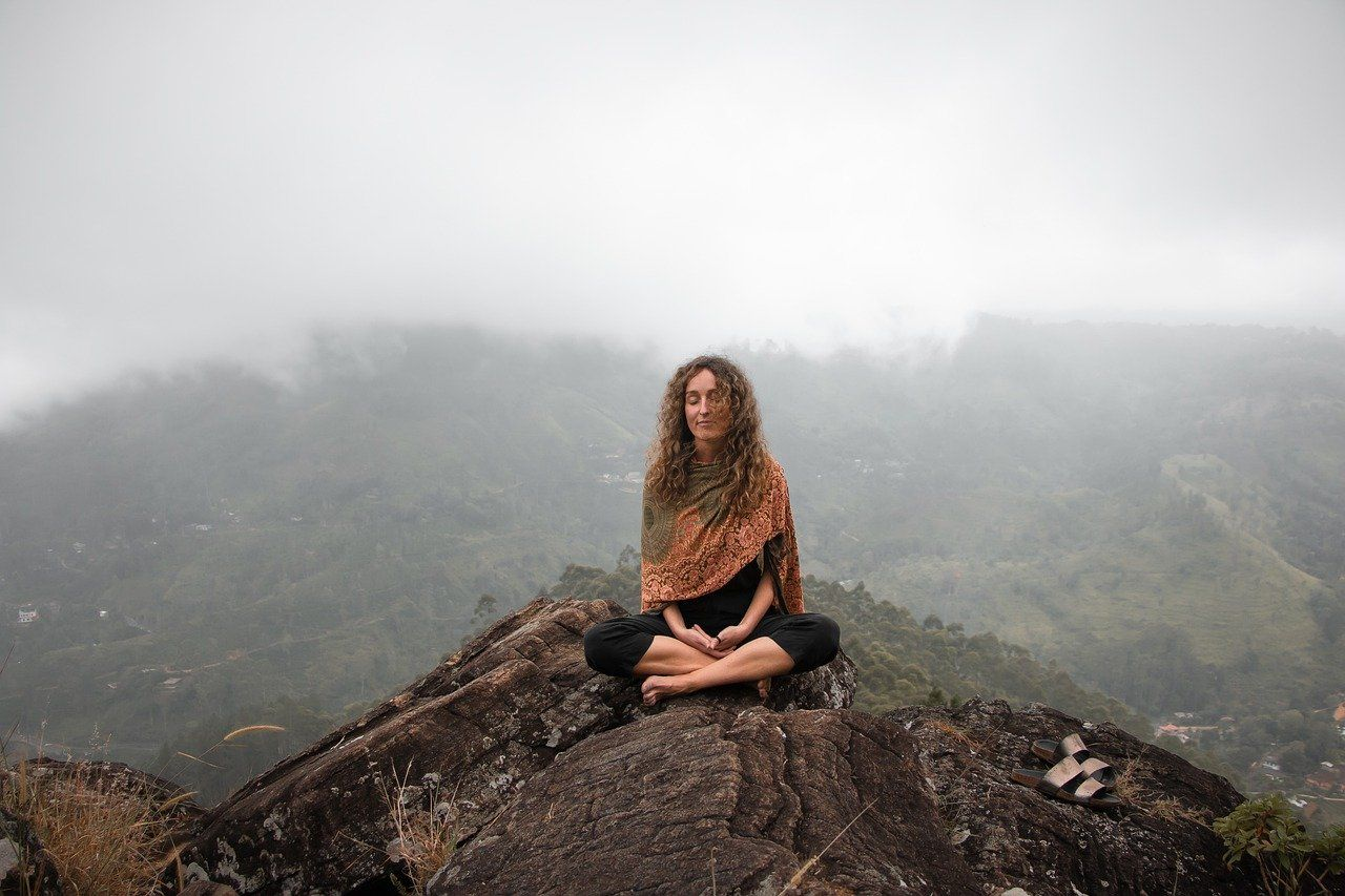 woman meditating on the hills
