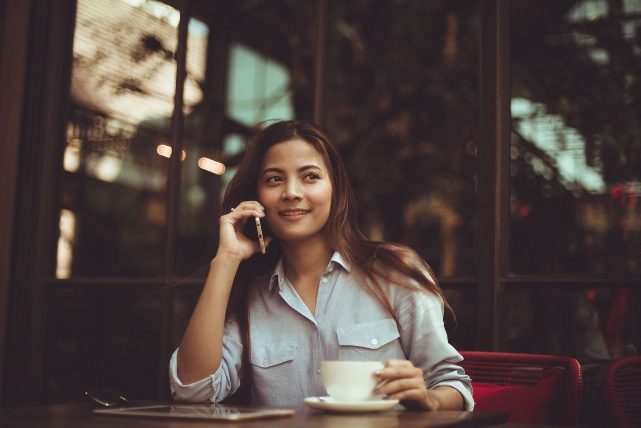woman talking on phone while drinking coffee