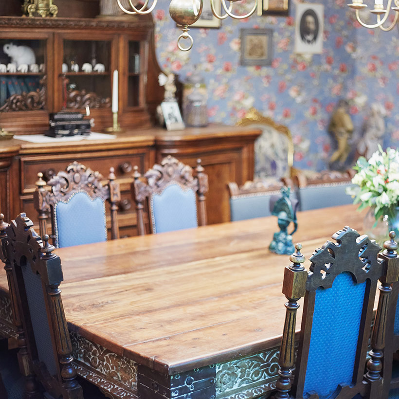 A dining room with a look and royal feel and showcase design for dining room and a sidewall with floral pattern