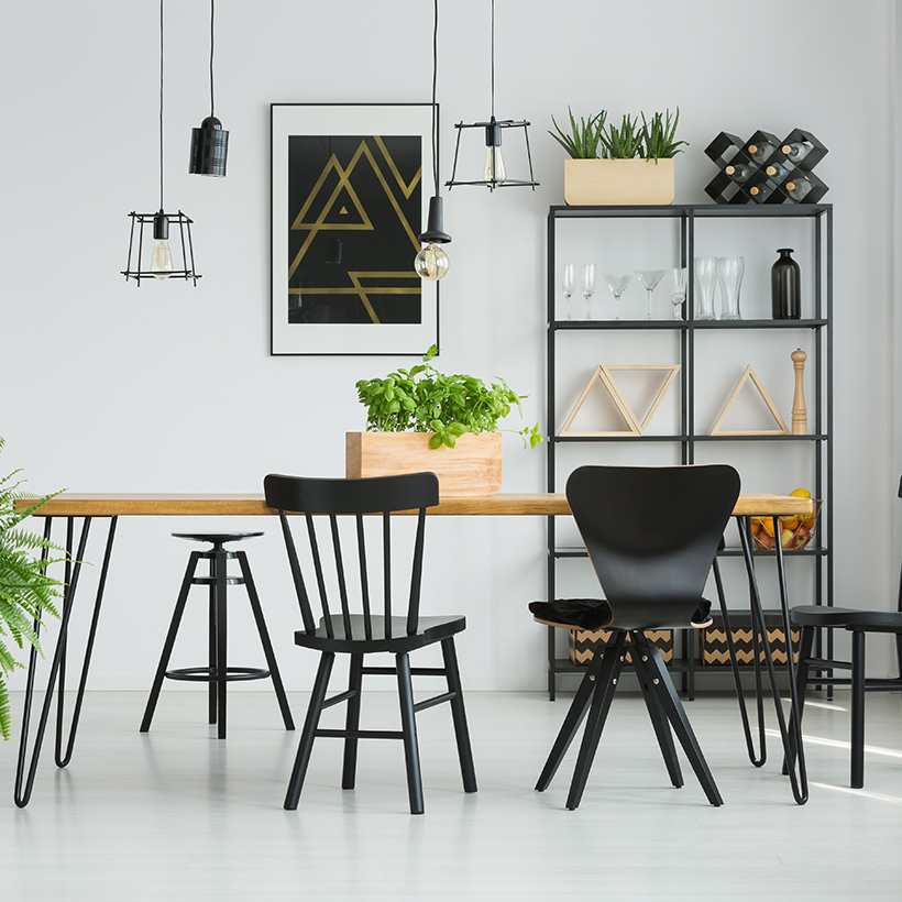 A dining room interior with a wooden dining table with a flower pot and and an open steel cabinet to keep glasses and bottles as modern dining room ideas
