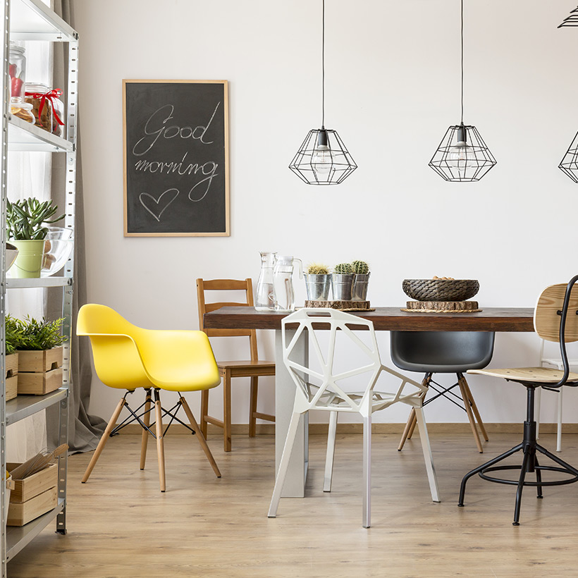 An elegant dining room design with all different types of chairs and hanging lights and a hanging chalk board with a fresh feel of plants around dining room furniture