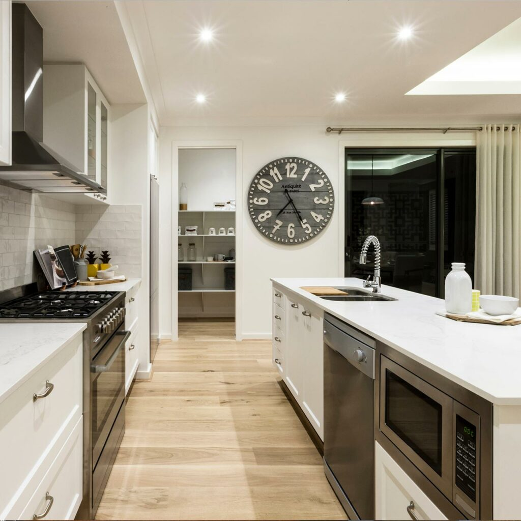 A white coloured parallel kitchen with two kitchens with sink countertop and gas countertop parallel to each other with a large clock hanging on the wall and a glass door of the balcony