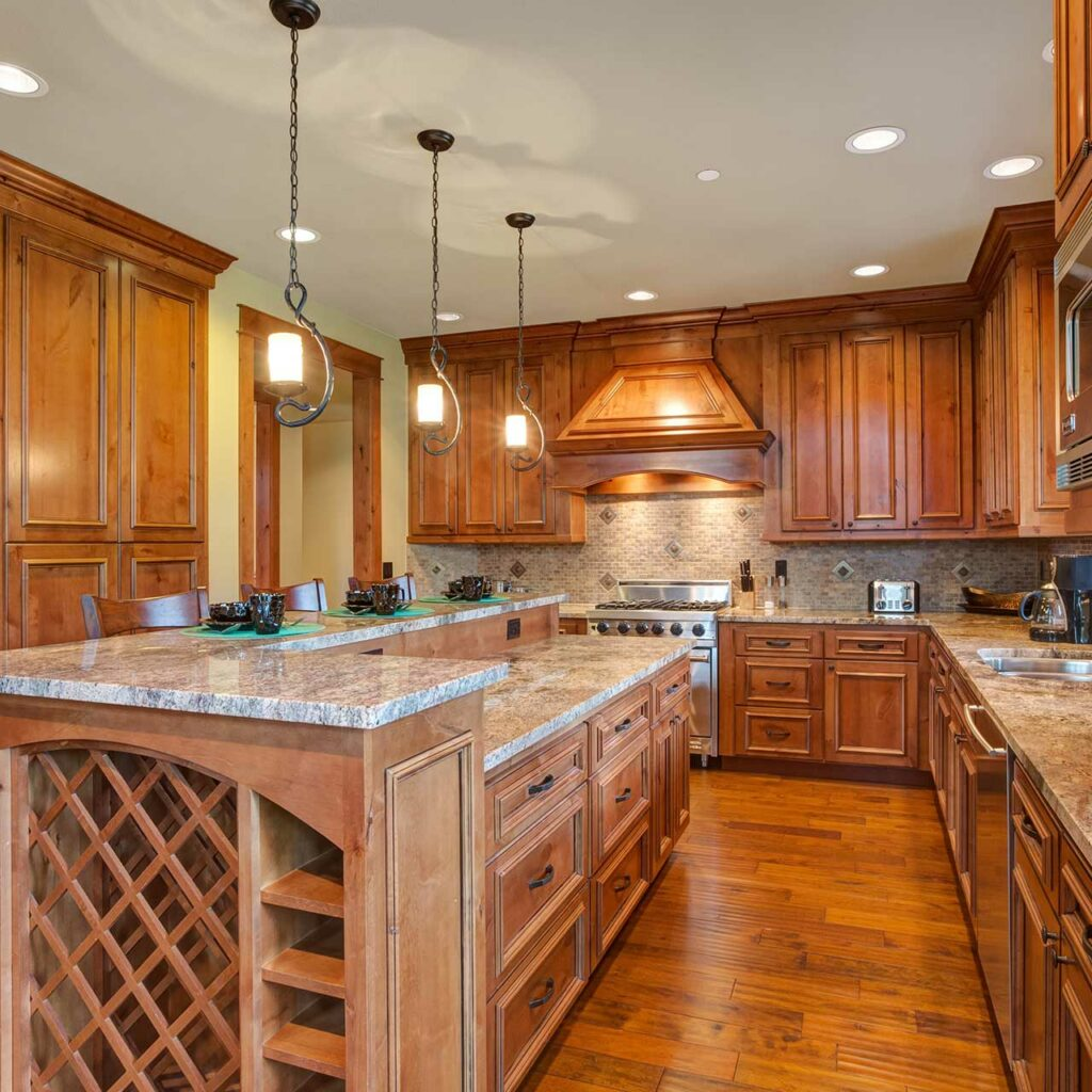 An Indian parallel kitchen interior design with an island in the middle and striking orange wooden finish with white marble countertop