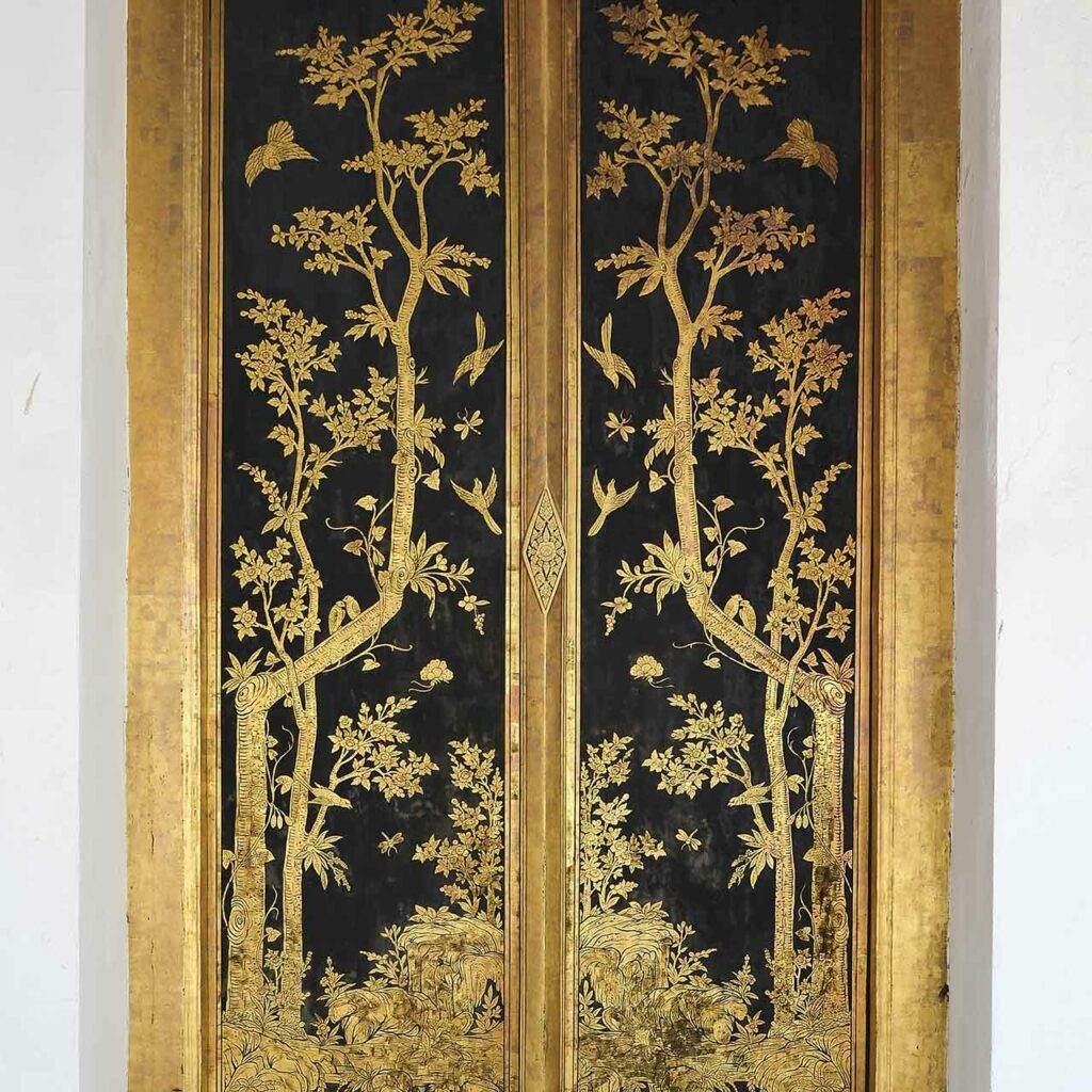 A gold coloured wooden door with prints which has all information as wooden pooja mandir design for home with price.