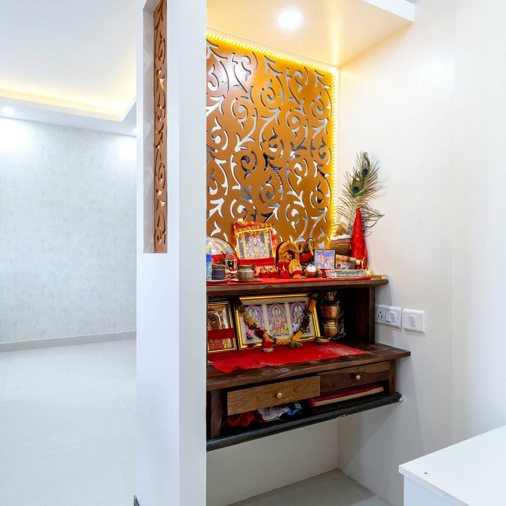 Temple design essentials on a white wall with a wooden shelf which is exactly a small wooden temple design for home