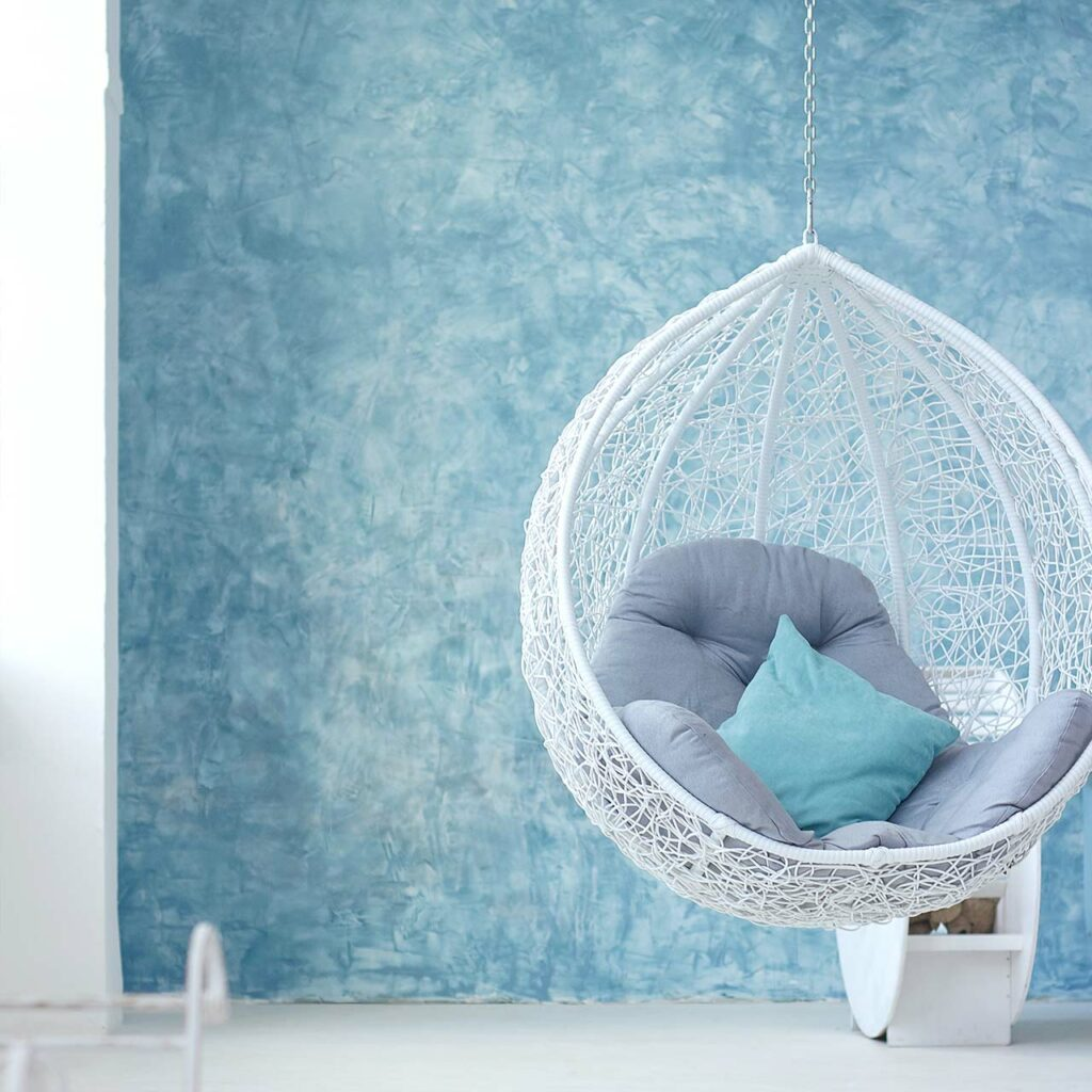 Hanging chair on a light blue wall in a small indian home