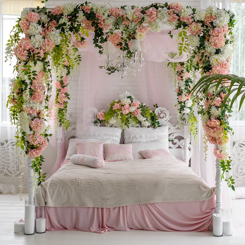 A beautiful canopy paired with flowers lends a chic touch to your romantic master bedroom design
