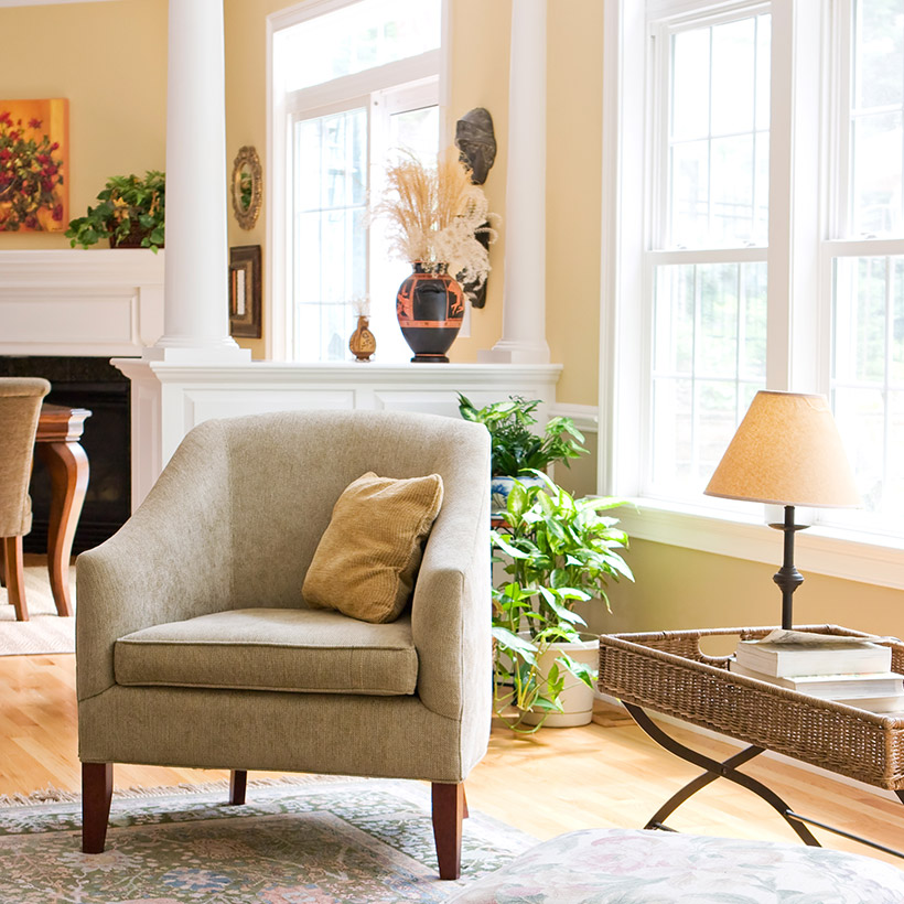 Indian living room india with a big sofa and big windows and a showcase with big pillars and a small table with books to read in a indian style living room