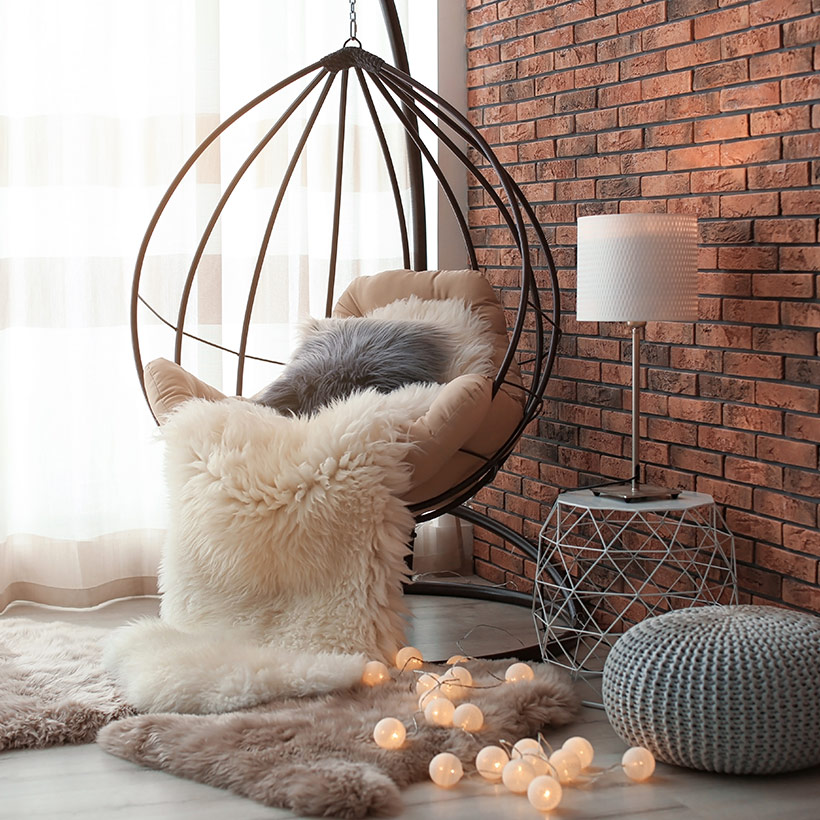 Living room designs indian style on a wall with rustic brick finish look and a large oval iron chair with cushion in a indian living room