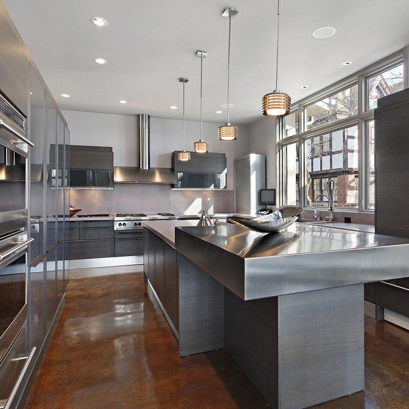 Stainless steel cabinets with hanging lamps made up of steel and countertop also made up of steel in kitchen wall cabinets
