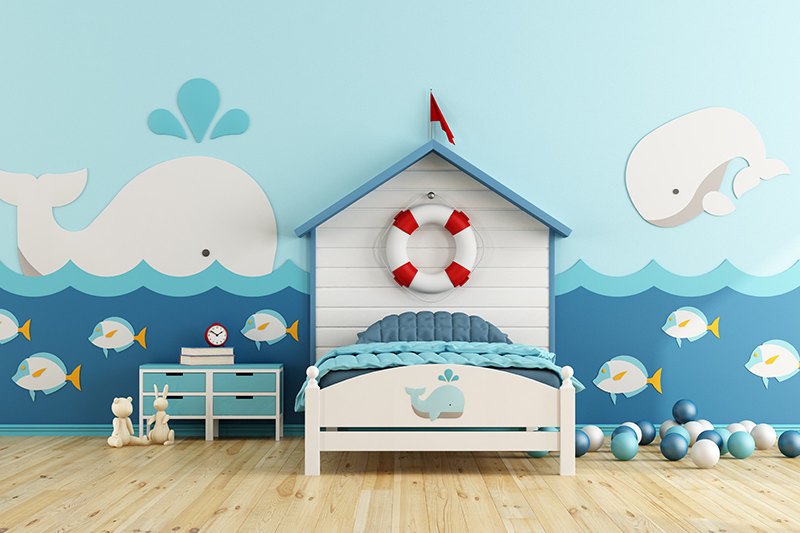 Kids wall decor with aa boat-shaped bed and stickers of whales and bubbly fish for kids room decor