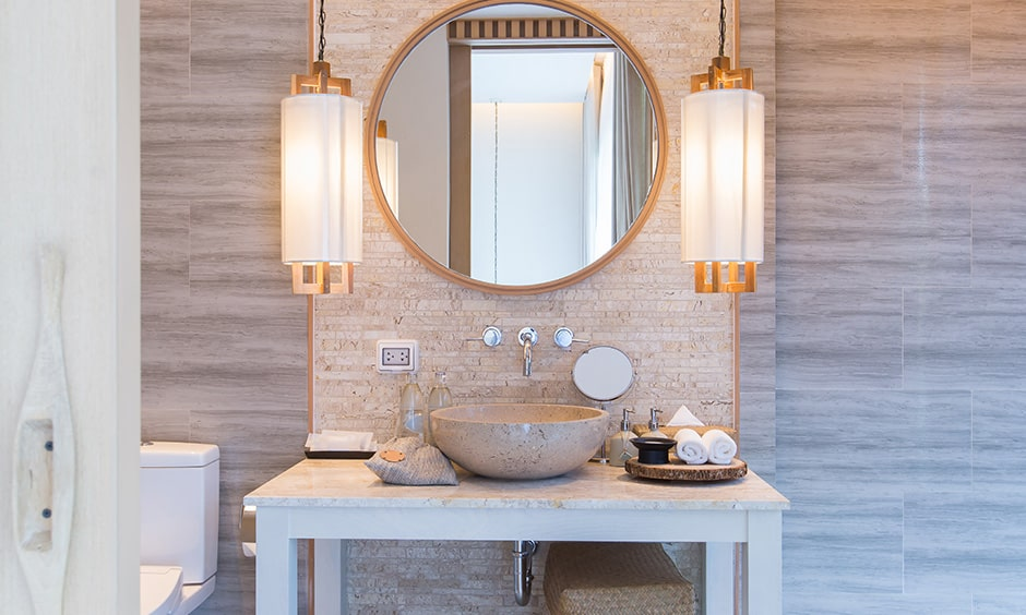Glass pendant bathroom lights with a textured wall and a decorative mirror