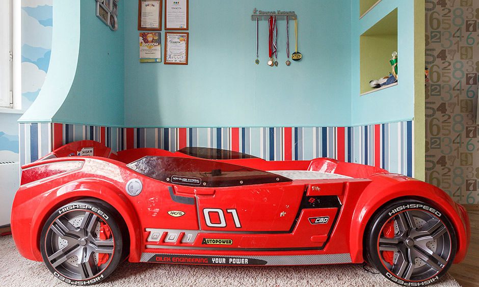 Modern kids bed design where a red-hot bed displays black rims, and a comfortable mattress Caption: