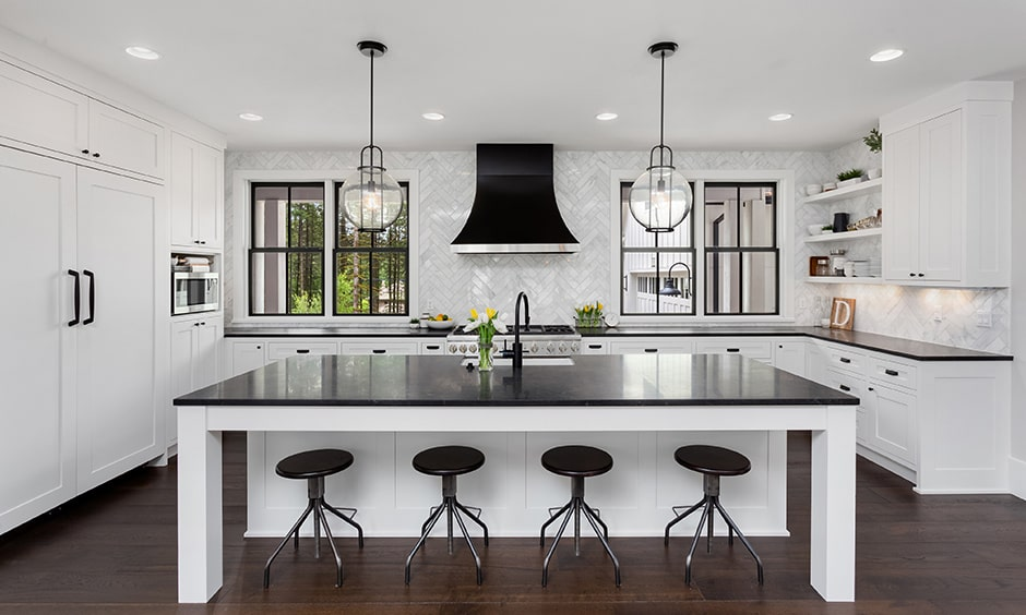 Luxurious black and white kitchen design with black island countertops, stools and sleek white cabinets