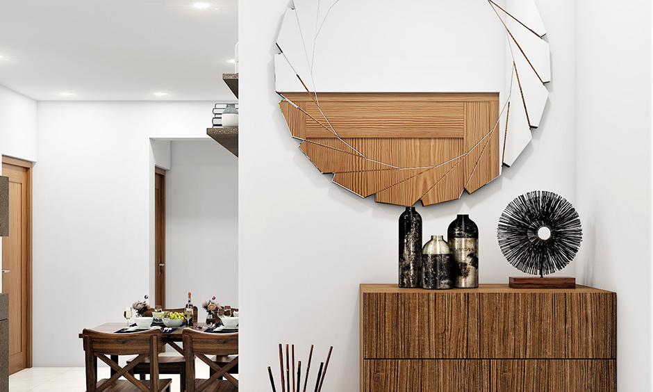 Round wall mirror design with cutting-edge, pinwheel-like design on the outer end looks sleek and creates visual drama
