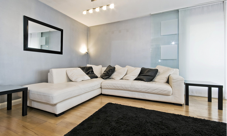 Simple rectangular wall mirror design with a black-finish slim metal frame is the ideal addition to a large living room.