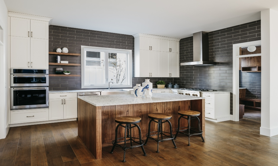Industrial kitchen island with stainless steel chimney, dark wooden bar chairs brings out an industrial vibe.