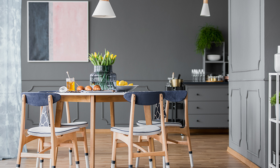 Grey coloured small dining room with cone-shaped pendant lights brings an industrial look.