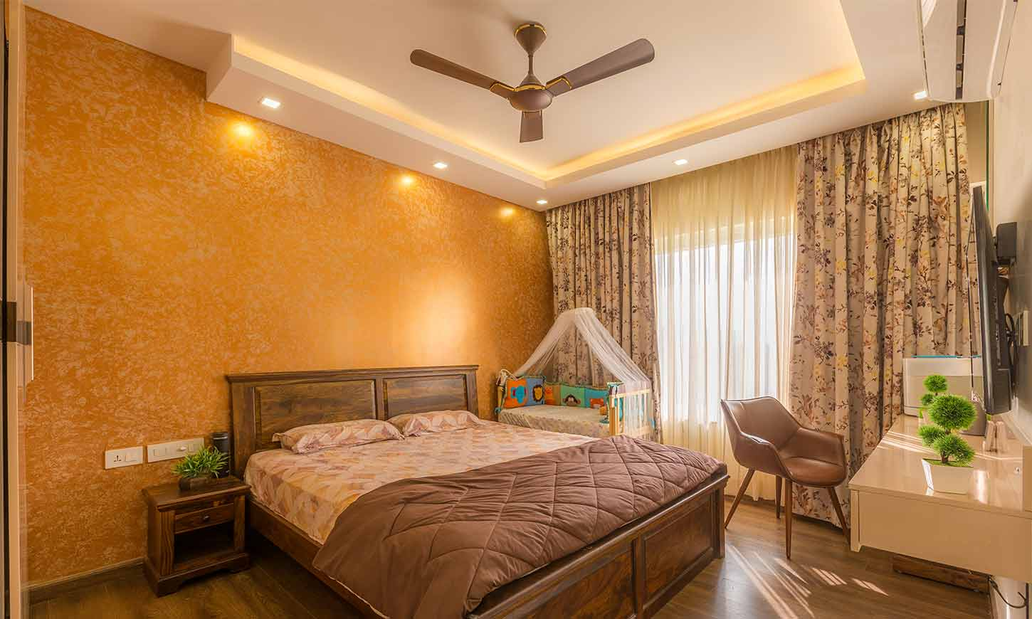 Bedroom interior design bangalore for rohan iksha apartment with a tv unit and a baby cot beside it