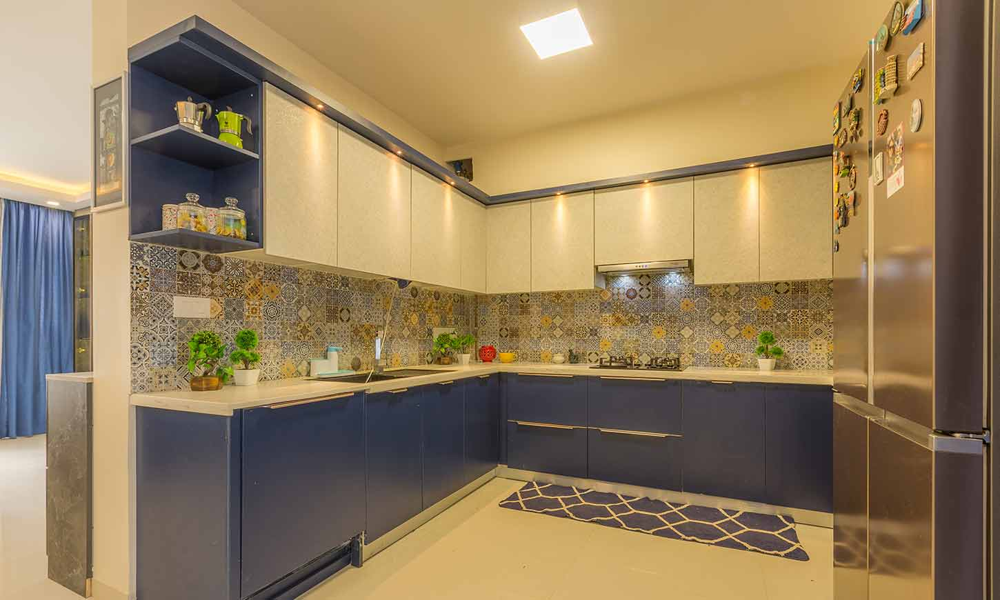 Modular kitchen price in bangalore with a blue and white kitchen designed by design cafe mg road