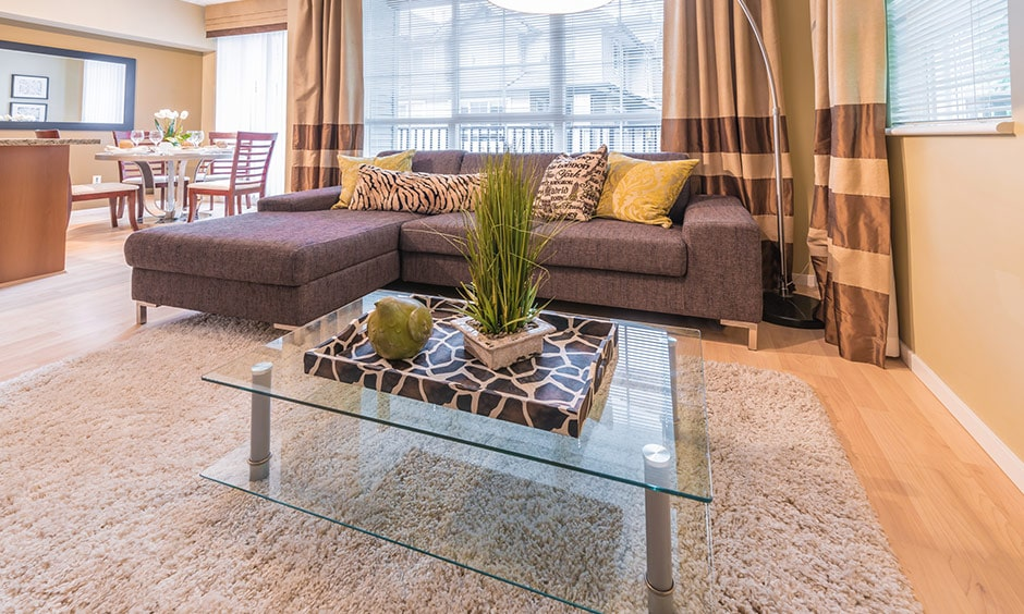 A glass finish coffee table for your living room with a lovely display of decor on it