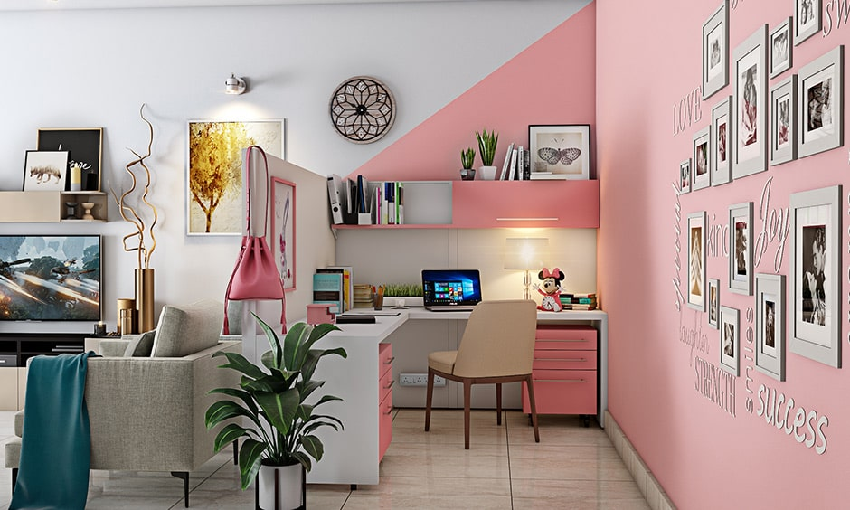 Pink cubicle design with photo frames on the wall and white and pink study table