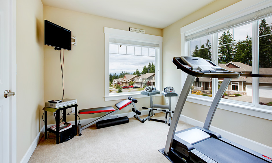Home gym design for small space with a view of the neighbourhood and carpet flooring