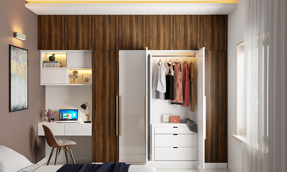 Shutter kids wardrobe with study table and bookshelf design is simple yet striking with a bold wood grain laminate.