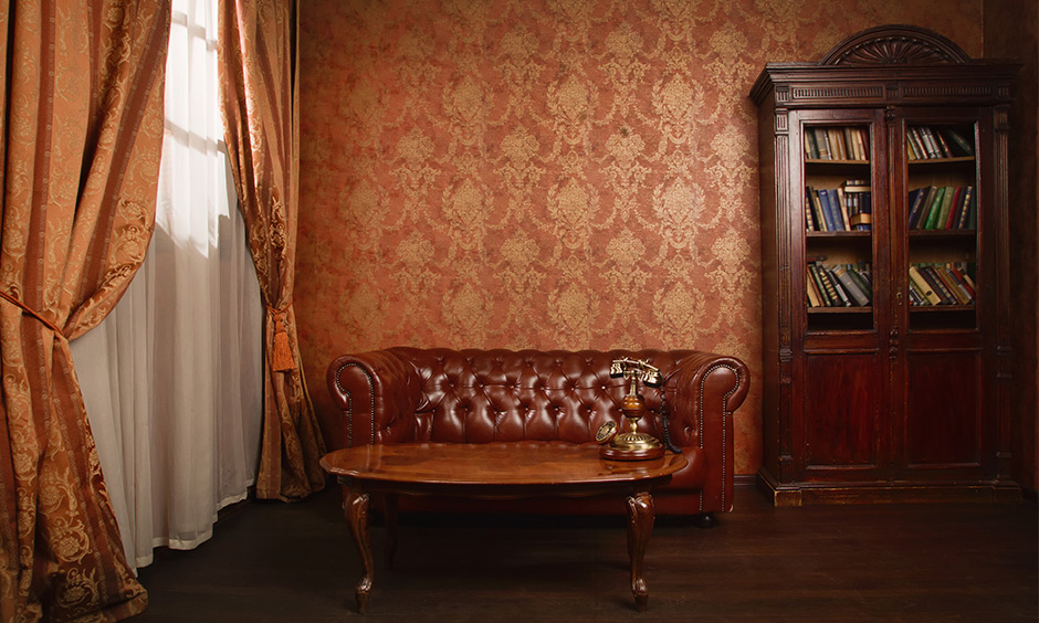 Brown gold wallpaper brings in old-world charm with elegant bookshelf and couch combined with other vintage furnishings