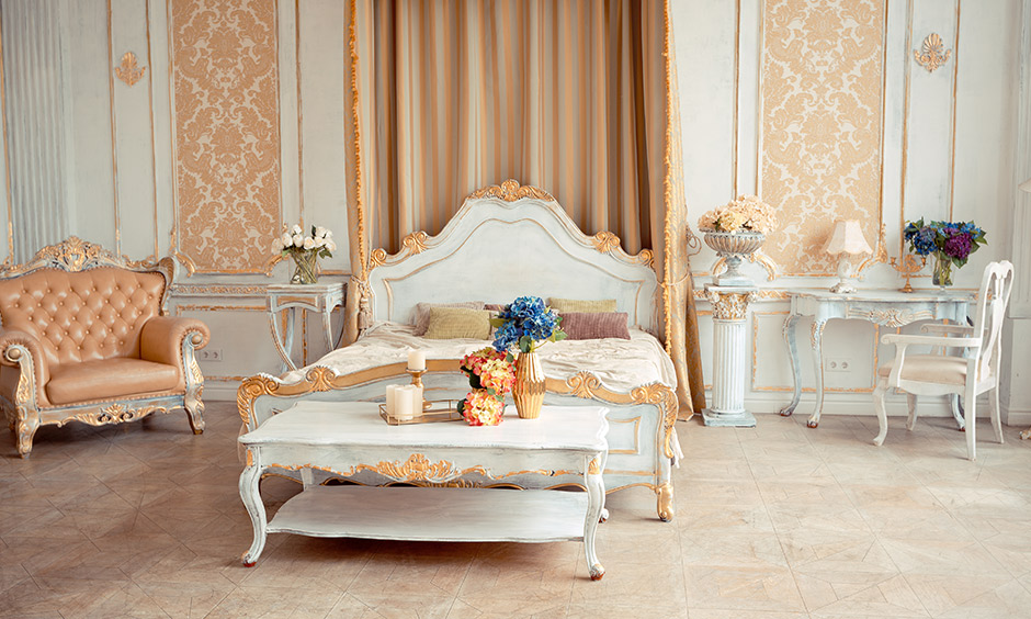 Two portions of the wall on either side of the bed covered with rose gold wallpaper look vintage style