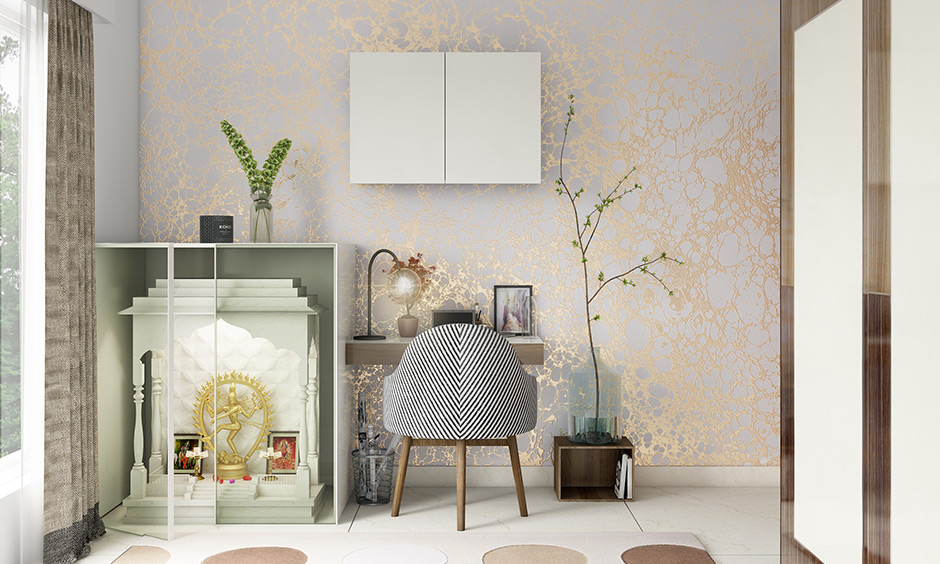 A pale white and gold wallpaper creates the right kind of aura around the pooja unit and study table