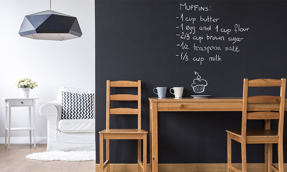 Minimal dining room decor with chalkboard paint on the wall gives dining room