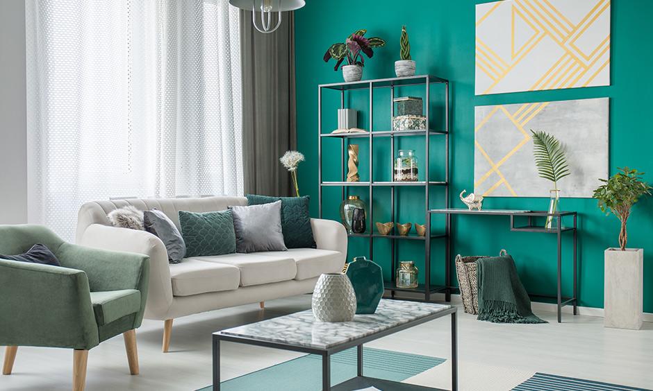 Emerald green living room accessories, indoor plants work as mesmerizing accessories & grants feel-good vibes.