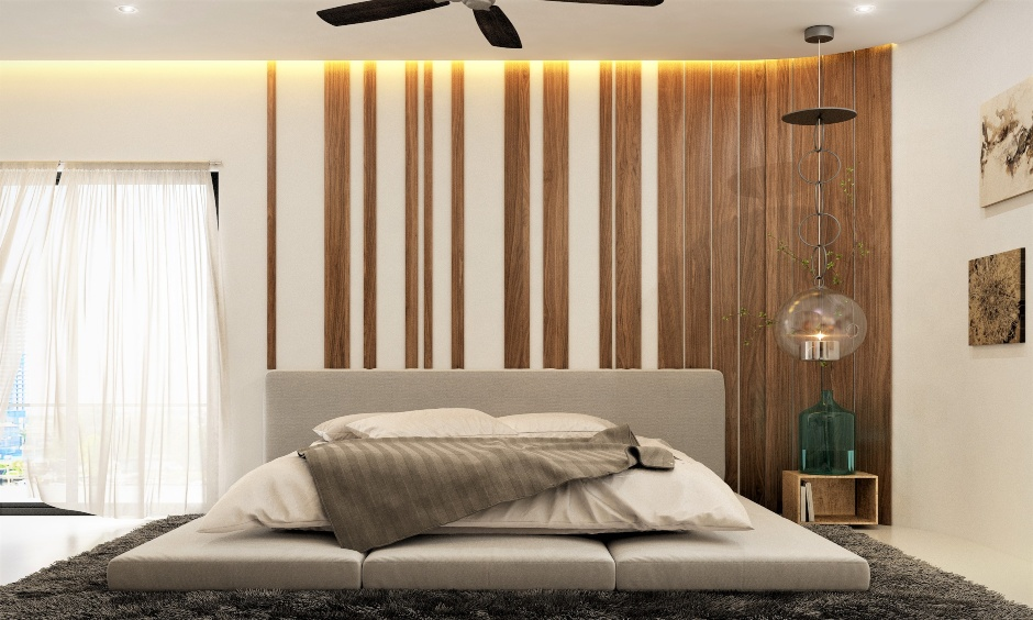 Frameless, double-layered low floor king-size bed with spaced-out effect wooden panelling on the back wall stands out.