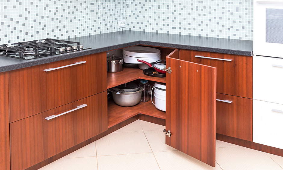 Modular kitchen corner cabinets with angular door and grey granite countertop exude warmth and cosiness.