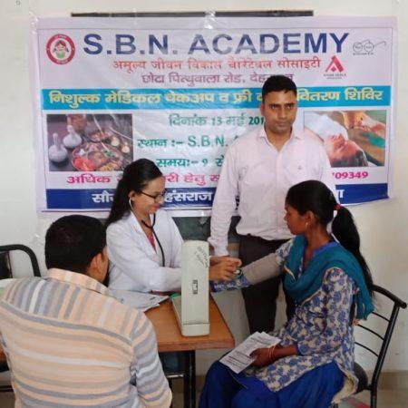 देहरादून के एसबीएन एकेडमी में आयोजित स्वास्थ्य शिविर में स्वास्थ्य परीक्षण करते चिकित्सक।