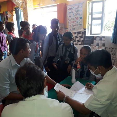 देहरादून के ग्लेक्शियन स्कूलमें आयोजित निःशुल्क स्वास्थ्य शिविर में स्वास्थ्य परीक्षण करते चिकित्सक।