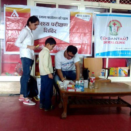 हमीरपुर के एम. पब्लिक स्कूल में आयोजित निःशुल्क स्वास्थ्य चिकित्सा शिविर में स्वास्थ्य परीक्षण करते चिकित्सक।