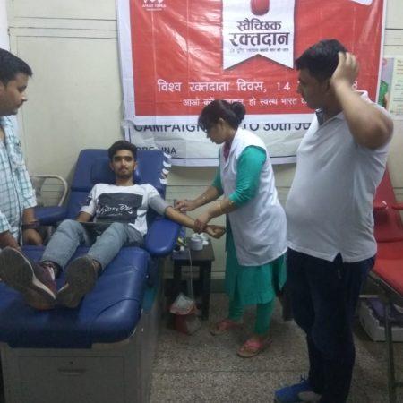 विश्व रक्तदाता दिवस के अवसर पर आयोजित रक्तदान शिविर में रक्तदान करता युवा।