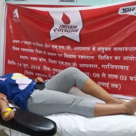 विश्व रक्तदाता दिवस के अवसर पर आयोजित रक्तदान शिविर में रक्तदान करती युवती।